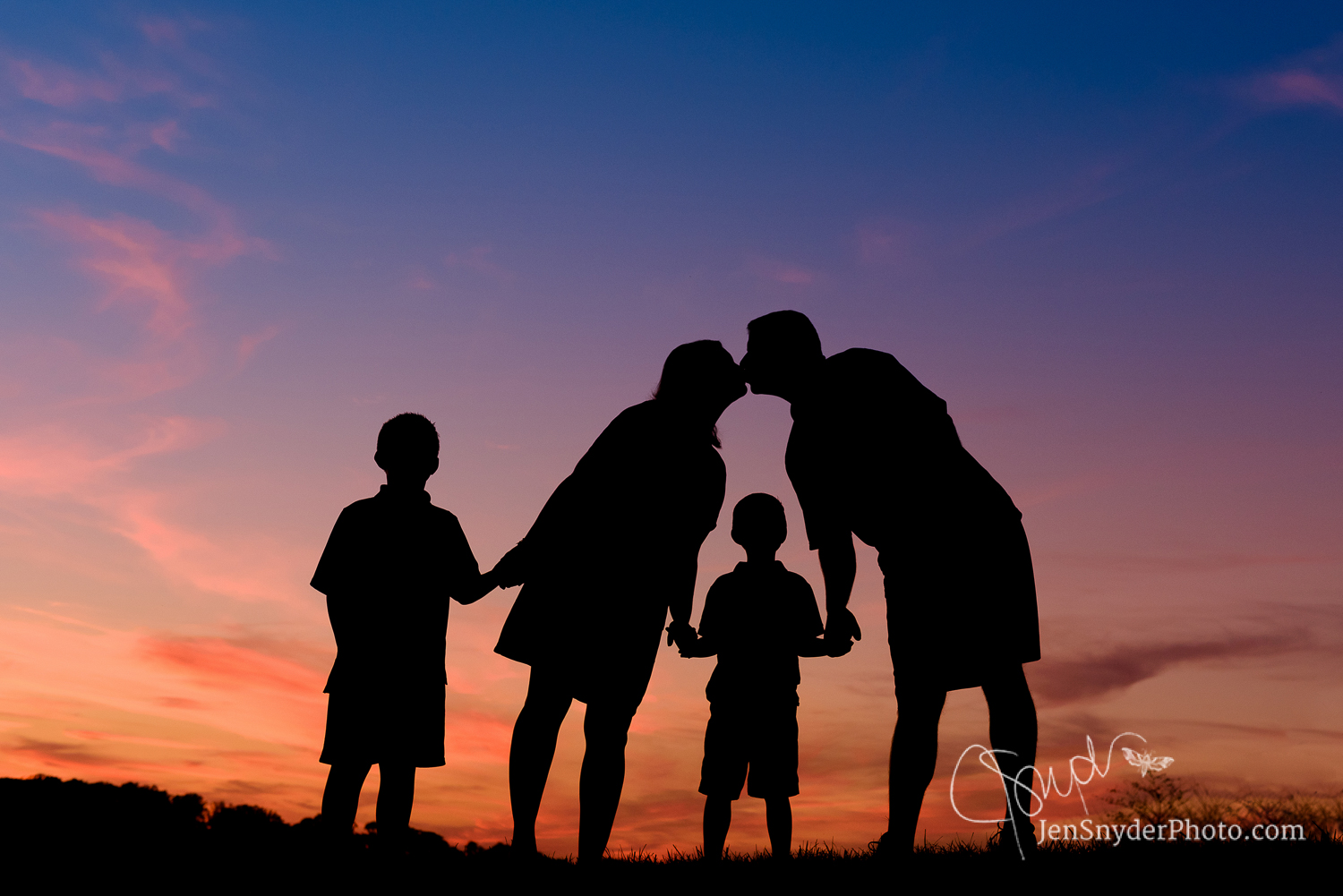 Baltimore, MD family portrait in silhouette against a summer sunset sky by professional photographer Jen Snyder http://www.jensnyderphoto.com